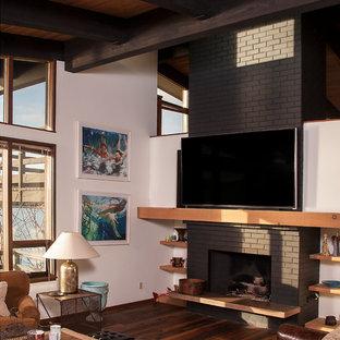 シアトルの広いコンテンポラリースタイルのおしゃれなオープンリビング (白い壁、濃色無垢フローリング、標準型暖炉、レンガの暖炉まわり、壁掛け型テレビ、茶色い床) の写真