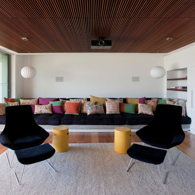 Example of a trendy light wood floor family room design in Sydney with white walls and no fireplace