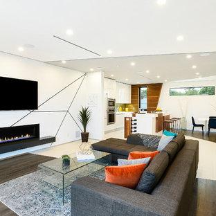 Ejemplo de sala de estar abierta, contemporánea, de tamaño medio, con paredes multicolor, suelo de madera oscura, chimenea lineal, televisor colgado en la pared, marco de chimenea de yeso y suelo marrón