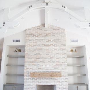 Diseño de sala de estar abierta, de estilo de casa de campo, de tamaño medio, con suelo de madera clara, chimenea tradicional y marco de chimenea de ladrillo