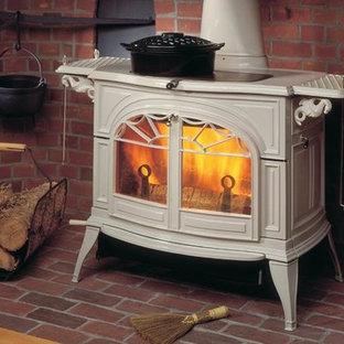 オレンジカウンティの中サイズのおしゃれなファミリールーム (レンガの床、薪ストーブ、金属の暖炉まわり、据え置き型テレビ、赤い床) の写真