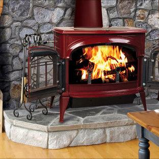 オレンジカウンティの中サイズのおしゃれなファミリールーム (淡色無垢フローリング、薪ストーブ、金属の暖炉まわり、据え置き型テレビ、茶色い床、黒い壁) の写真