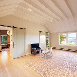 Foto de sala de juegos en casa abierta, de estilo de casa de campo, de tamaño medio, sin chimenea, con paredes blancas, suelo de madera clara y televisor independiente