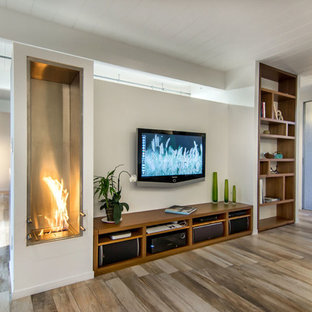 This is an example of a mid-sized midcentury open concept family room in San Francisco with white walls, a metal fireplace surround, a wall-mounted tv, a ribbon fireplace, porcelain floors and beige floor.