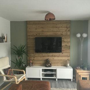 Inspiration pour une petite salle de séjour ethnique fermée avec un mur vert, un sol en carrelage de céramique, un téléviseur fixé au mur et un sol gris.