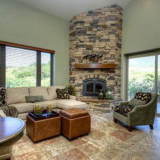 Exemple d'une grande salle de séjour chic ouverte avec un mur vert, un sol en travertin, une cheminée d'angle, un manteau de cheminée en pierre et aucun téléviseur.