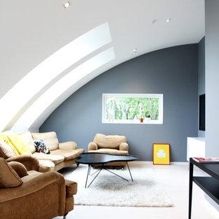 Großes, Abgetrenntes Nordisches Wohnzimmer ohne Kamin mit grauer Wandfarbe, gebeiztem Holzboden und Wand-TV in Göteborg