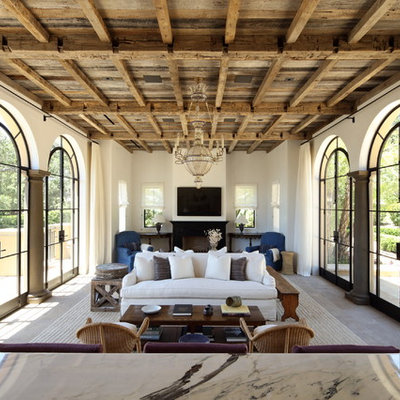 Example of a tuscan family room design in Los Angeles with white walls, a standard fireplace and a wall-mounted tv