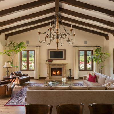 Tuscan dark wood floor and brown floor family room photo in San Francisco with beige walls and a standard fireplace