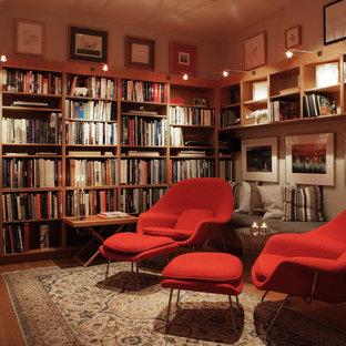 オースティンの中サイズのコンテンポラリースタイルのおしゃれな独立型ファミリールーム (無垢フローリング、壁掛け型テレビ、ライブラリー、ベージュの壁、暖炉なし、茶色い床) の写真