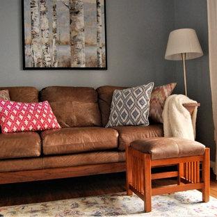 バンクーバーの小さいコンテンポラリースタイルのおしゃれな独立型ファミリールーム (青い壁、クッションフロア、据え置き型テレビ、茶色い床) の写真