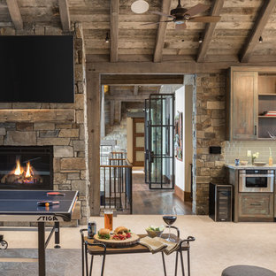 Inspiration for a rustic open concept dark wood floor and brown floor game room remodel in Jackson with a standard fireplace, a stone fireplace and a wall-mounted tv