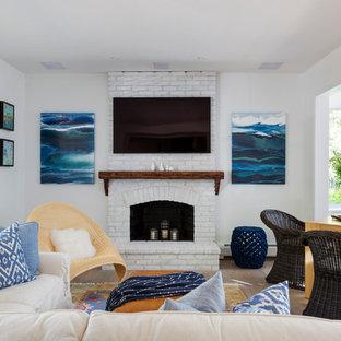 ボストンの中サイズのビーチスタイルのおしゃれなファミリールーム (ゲームルーム、白い壁、淡色無垢フローリング、標準型暖炉、レンガの暖炉まわり、壁掛け型テレビ) の写真