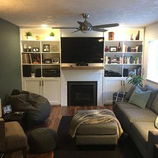 バンクーバーの中サイズのモダンスタイルのおしゃれな独立型ファミリールーム (グレーの壁、クッションフロア、タイルの暖炉まわり、壁掛け型テレビ、茶色い床) の写真
