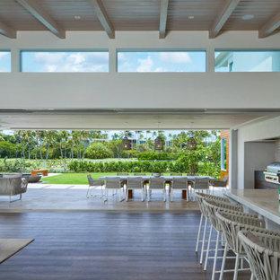 Esempio di un soggiorno tropicale di medie dimensioni e aperto con pavimento in legno massello medio, pavimento marrone, travi a vista e pareti in legno