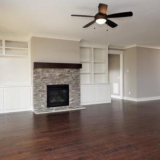 Idee per un grande soggiorno tradizionale aperto con pareti grigie, camino classico, cornice del camino in pietra, pavimento marrone e pavimento in vinile