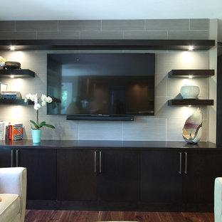 Diseño de sala de estar abierta, minimalista, de tamaño medio, con paredes grises, suelo de madera en tonos medios, televisor colgado en la pared y suelo marrón