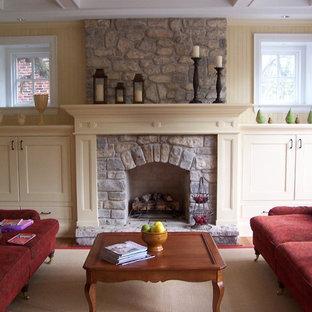 Imagen de sala de estar abierta, clásica, pequeña, con paredes amarillas, suelo de madera en tonos medios, chimenea tradicional y marco de chimenea de piedra