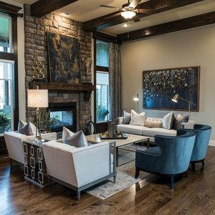 Exemple d'une grand salle de séjour chic ouverte avec un mur beige, une cheminée double-face, un manteau de cheminée en pierre, un bar de salon, un sol en bois foncé, aucun téléviseur et un sol marron.