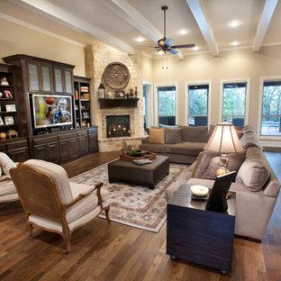 オースティンの大きいトラディショナルスタイルのおしゃれなファミリールーム (ベージュの壁、無垢フローリング、標準型暖炉、石材の暖炉まわり、埋込式メディアウォール、茶色い床) の写真