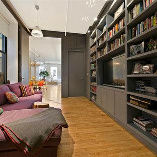 Immagine di un piccolo soggiorno industriale chiuso con libreria, pareti nere, parquet chiaro, nessun camino e TV a parete