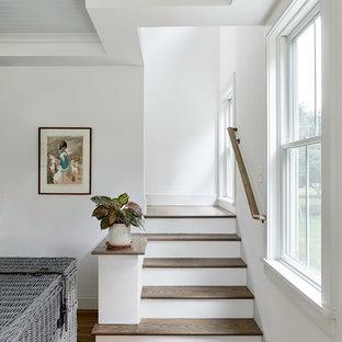 Imagen de sala de estar abierta, campestre, grande, sin chimenea, con paredes blancas, suelo de madera clara, televisor colgado en la pared y suelo marrón