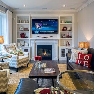 Ejemplo de sala de estar abierta, tradicional renovada, de tamaño medio, con paredes grises, suelo de madera pintada, chimenea tradicional, marco de chimenea de madera y televisor colgado en la pared