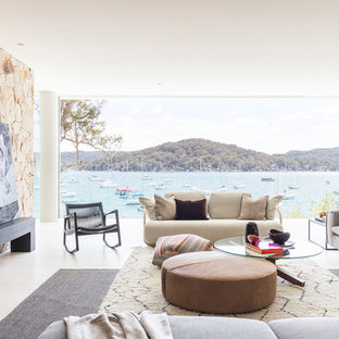 This is an example of a beach style family room in Sydney with white walls and white floor.