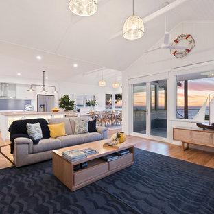 パースの大きいビーチスタイルのおしゃれなファミリールーム (白い壁、無垢フローリング、コーナー設置型暖炉、木材の暖炉まわり、壁掛け型テレビ) の写真
