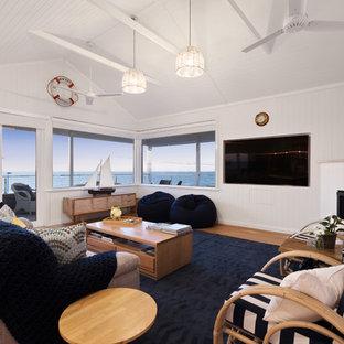 パースの広いビーチスタイルのおしゃれなオープンリビング (白い壁、無垢フローリング、コーナー設置型暖炉、木材の暖炉まわり、壁掛け型テレビ) の写真