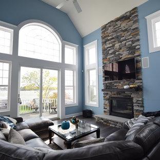 ニューヨークの大きいモダンスタイルのおしゃれなファミリールーム (青い壁、濃色無垢フローリング、標準型暖炉、石材の暖炉まわり、内蔵型テレビ、グレーの床) の写真