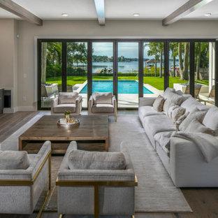 Geräumiges, Offenes Modernes Wohnzimmer mit weißer Wandfarbe, braunem Holzboden, braunem Boden, Kaminumrandung aus Holzdielen, Wand-TV und freigelegten Dachbalken in Tampa
