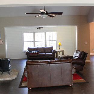 Diseño de sala de estar abierta, tradicional, de tamaño medio, con paredes beige, suelo de madera oscura, estufa de leña, marco de chimenea de ladrillo, televisor independiente y suelo marrón