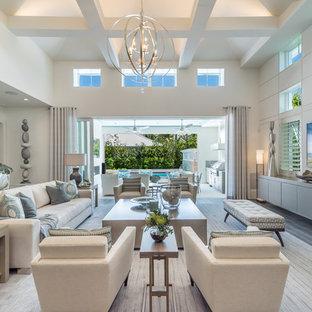 Ejemplo de sala de estar abierta, costera, sin chimenea, con paredes blancas, suelo de madera oscura y televisor colgado en la pared