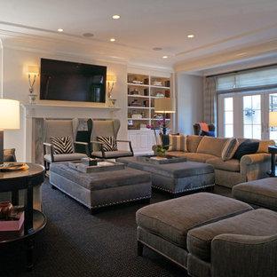 Modelo de sala de estar cerrada, clásica, grande, con paredes blancas, suelo de madera oscura, chimenea tradicional, marco de chimenea de piedra y televisor colgado en la pared