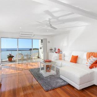 他の地域のビーチスタイルのおしゃれなファミリールーム (白い壁、無垢フローリング、オレンジの床) の写真
