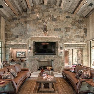 Immagine di un soggiorno stile rurale con pareti marroni, camino classico, cornice del camino in pietra e TV a parete