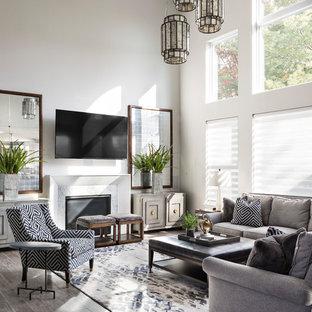 Foto di un soggiorno tradizionale aperto con pareti bianche, camino classico, cornice del camino in pietra, TV a parete e pavimento grigio