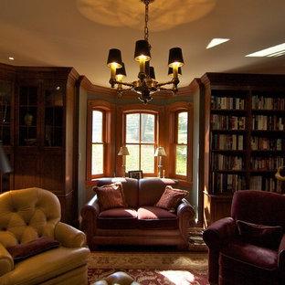 Ejemplo de sala de estar con biblioteca cerrada, campestre, con paredes marrones y suelo de madera oscura