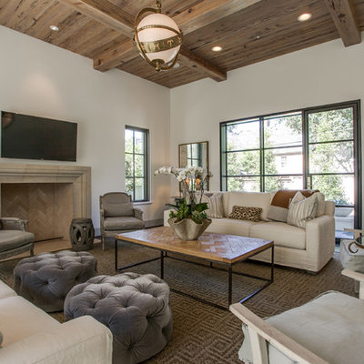 Example of a transitional family room design in Dallas with beige walls, a standard fireplace, a stone fireplace and a wall-mounted tv
