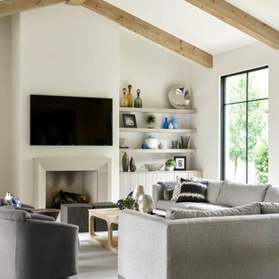 Example of a trendy carpeted and gray floor family room design in Dallas with white walls, a standard fireplace and a wall-mounted tv