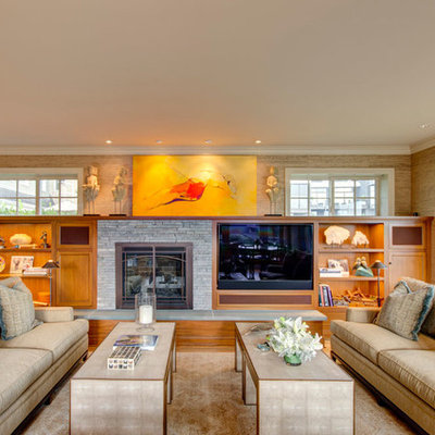Elegant family room photo in Portland with beige walls, a standard fireplace, a stone fireplace and a media wall