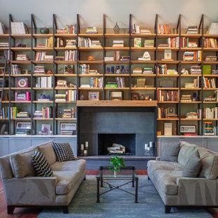 Idée de décoration pour une salle de séjour avec une bibliothèque ou un coin lecture tradition avec une cheminée standard, un manteau de cheminée en métal, un mur vert, un sol en bois brun et un sol marron.