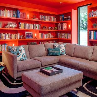 オースティンのコンテンポラリースタイルのおしゃれなファミリールーム (ライブラリー、赤い壁) の写真