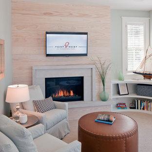 グランドラピッズの中くらいのビーチスタイルのおしゃれなオープンリビング (緑の壁、カーペット敷き、標準型暖炉、石材の暖炉まわり、壁掛け型テレビ、茶色い床) の写真
