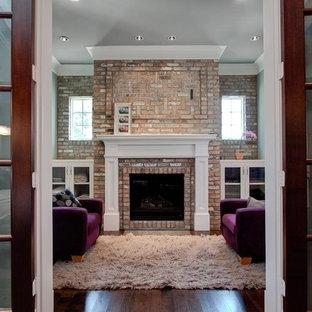 Ejemplo de sala de estar clásica con marco de chimenea de ladrillo y televisor retractable