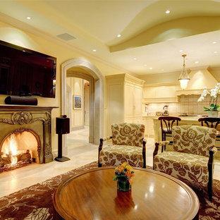 Esempio di un soggiorno mediterraneo aperto con pareti beige, pavimento in pietra calcarea, camino classico, cornice del camino in metallo e TV a parete