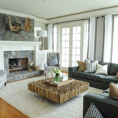 Family room - large coastal open concept medium tone wood floor and brown floor family room idea in Vancouver with a standard fireplace, a stone fireplace, gray walls and a wall-mounted tv
