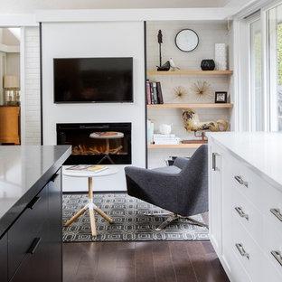 Cette image montre une petite salle de séjour vintage ouverte avec un mur blanc, un sol en bois foncé, cheminée suspendue, un manteau de cheminée en plâtre, un téléviseur fixé au mur et un sol marron.