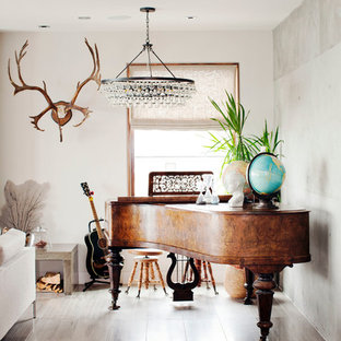Inspiration for a large eclectic light wood floor and brown floor family room remodel in Vancouver with a music area, beige walls and no fireplace
